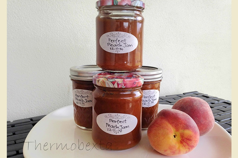 four jars thermomix peach jam on a white plate with white background. Peaches beside them.