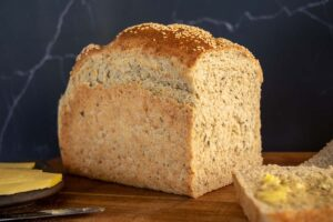 cut loaf side on, super seeded thermomix wholemeal multigrain bread loaf. Black background. Wooden tabletop