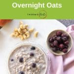 thermomix overnight oats on white board with mauve fabric, blueberries and cashews surrounding