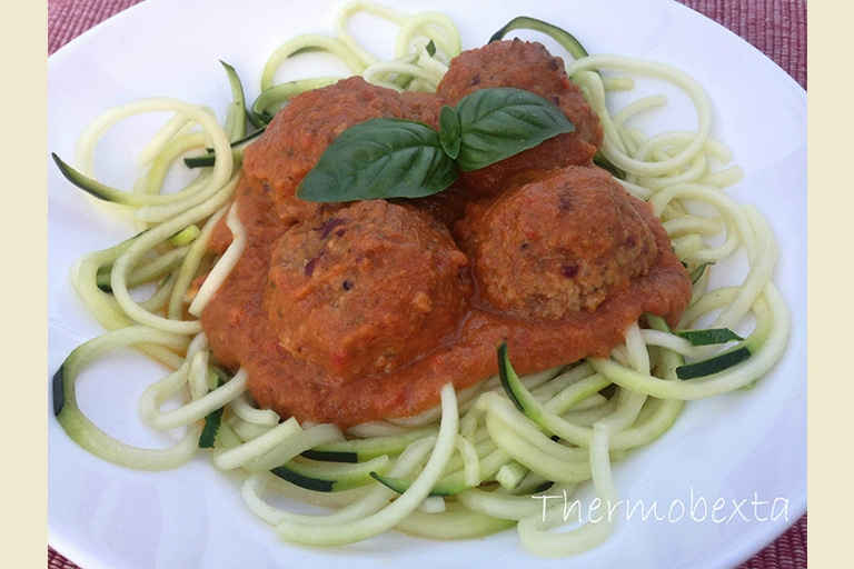 Four meatballs on top of zoodles, topped with tomato sauce and two basil leaves. On white plate.