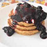 thermomix blueberry sauce drizzled over pancake stack on white plate