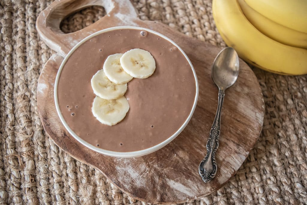 choc banana custard in bowl with four slices of banana on top, sitting on rustic wooden board on woven placemat, two bananas off to the side