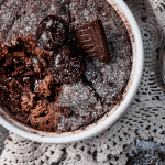 thermomix choc pudding in white bowl, with doily and spoon