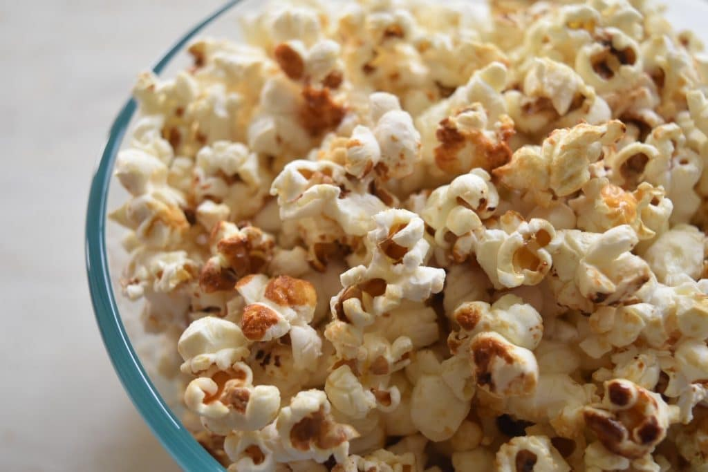 sweet and salty popcorn in glass bowl on white surface