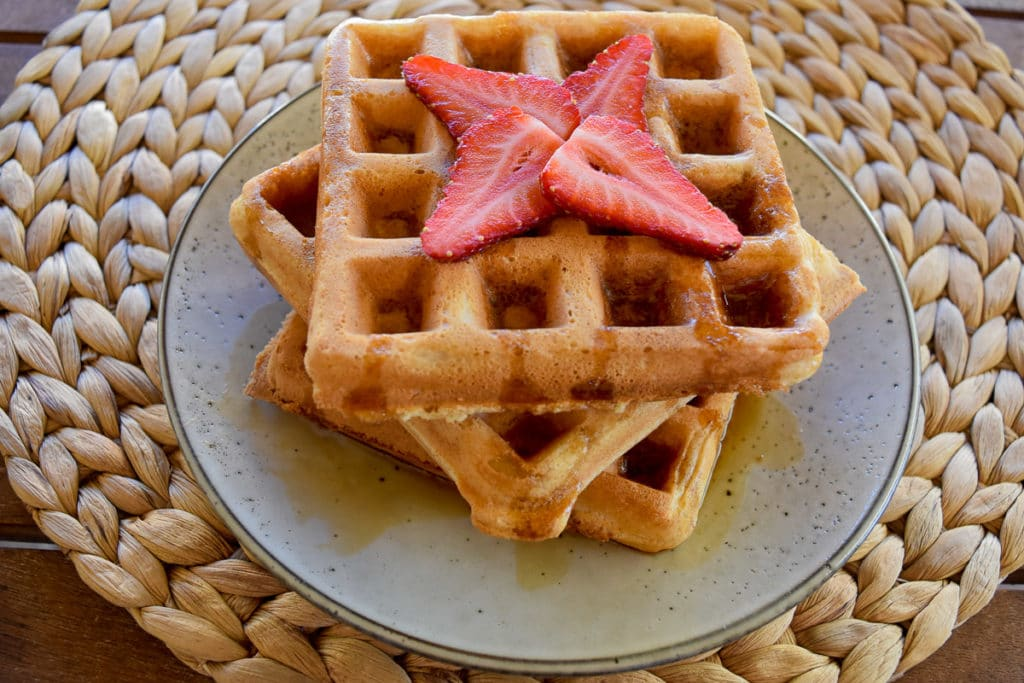 three thermomix waffles on grey plate on straw woven round placemat. Maple syrup and strawberries on top of waffles