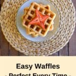 pin three thermomix waffles from birds eye view with maple syrup and strawberries on woven placemat on wooden table