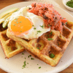 savoury waffles thermomix on white plate topped with fried egg and salsa, fork and parsley in background