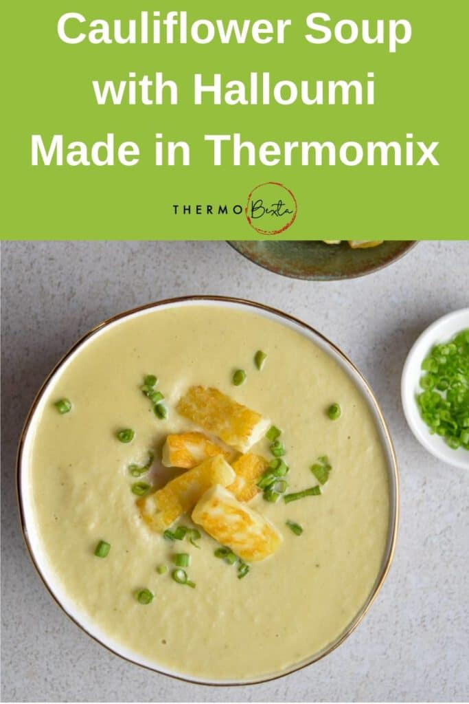cauliflower soup in gold rimmed bowl with halloumi and chives on top, grey tabletop