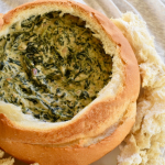 thermomix spinach cob loaf dip in cob loaf. Cream background with chunks of crusty bread around