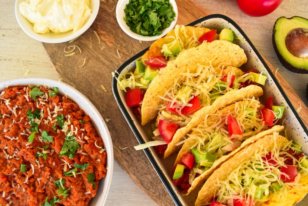 plate of tacos, bowl of taco filling next to it with other ingredients around