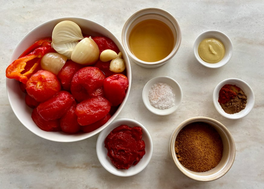 large bowl of tomatoes, smaller bowls of other thermomix tomato ketchup ingredients