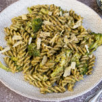Pesto pasta and broccoli on white plate with grey detail. Rustic dark background, small bowl of cheese in background