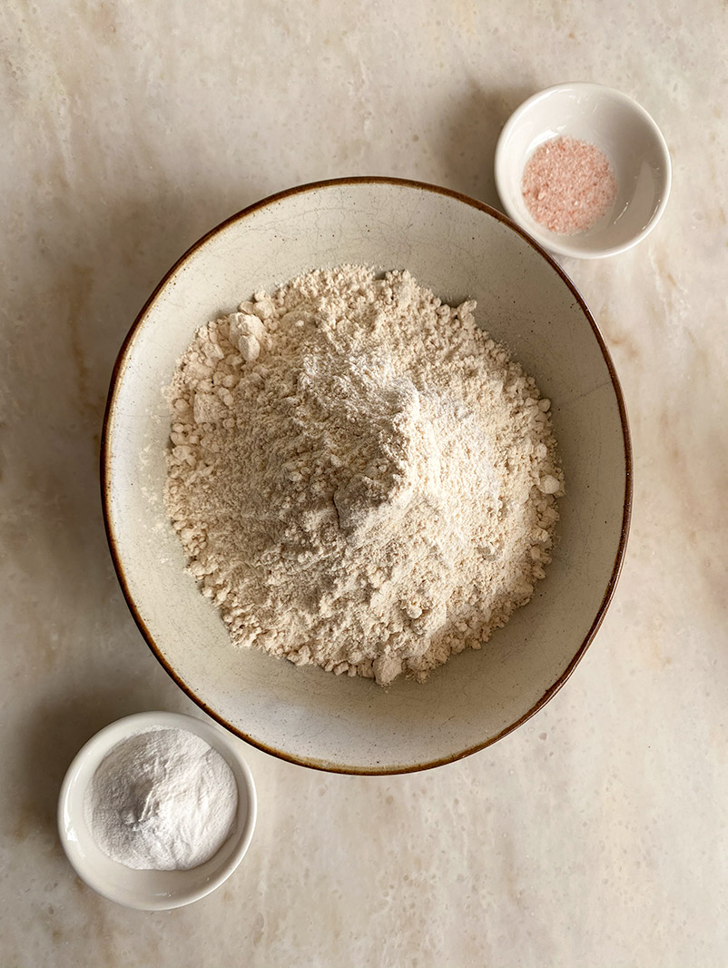 flour, baking powder and salt in separate dishes on white bench