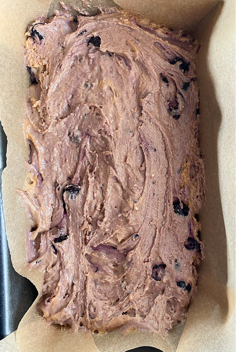 blueberry and lemon loaf batter raw in lined loaf tin