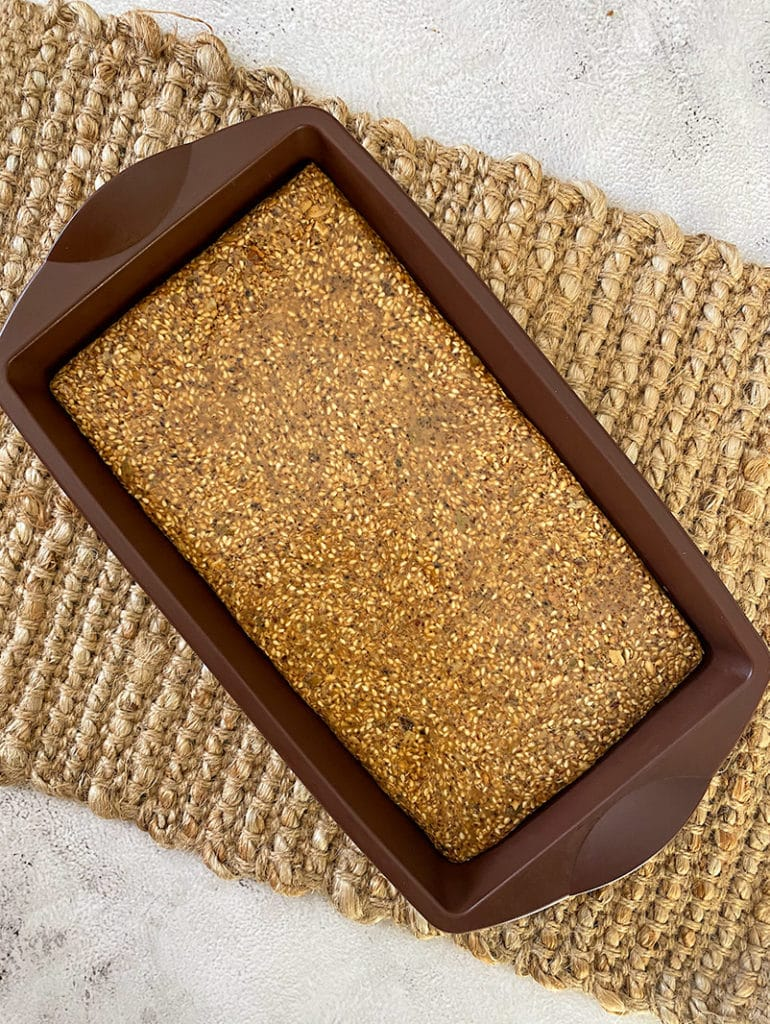 sesame bars in brown silicon slice form, on woven placemat, on grey table
