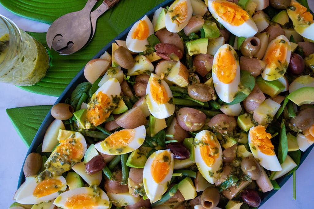 Salad of spinach, potatoes, avocado, boiled eggs, olives, on blue platter sitting on green leaf placemat on white tabletop, above platter are a set of salad servers and a jar containing yellow and green dressing