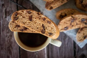 two slices choc chip biscotti made in Thermomix, sitting on top of white mug of black coffee. Sitting on wooden dark surface, with more biscotti in background, blurred.