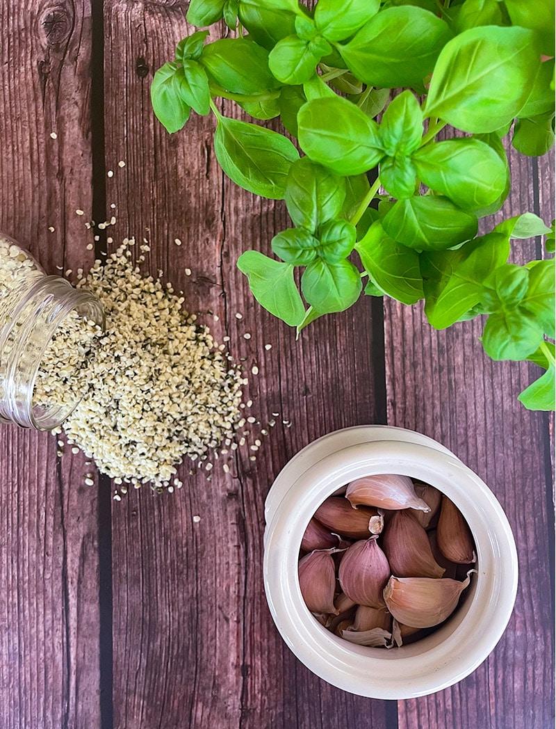 ingredients flat lay for hemp seed basil pesto on wooden table - basil, garlic, hemp seeds