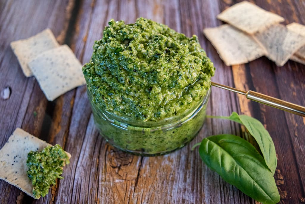 overflowing jar of hemp seed basil pesto, gold spoon handle sticking out, surrounded by crackers, two basil leaves in forefront