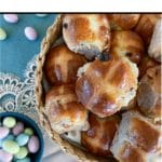 hot cross buns in basket with candied Easter eggs off to the side