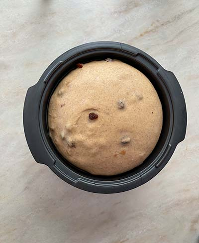 hot cross buns dough in black bowl on stone bench top, after rising