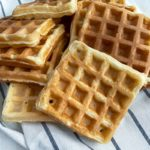 pile of several thermomix waffles laying on striped white and blue tea towel