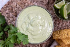 lime coriander cashew sauce in a bowl, on brown placemat. Fresh coriander and lime and corn chips