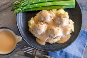 grey tabletop, with black bowl of mashed potato, vegetarian meatballs and Swedish cream sauce gravy, a few pieces of asparagus at back of plate. Small pouring jug bottom left with cream sauce in. Knife and fork and blue serviette front middle and right.