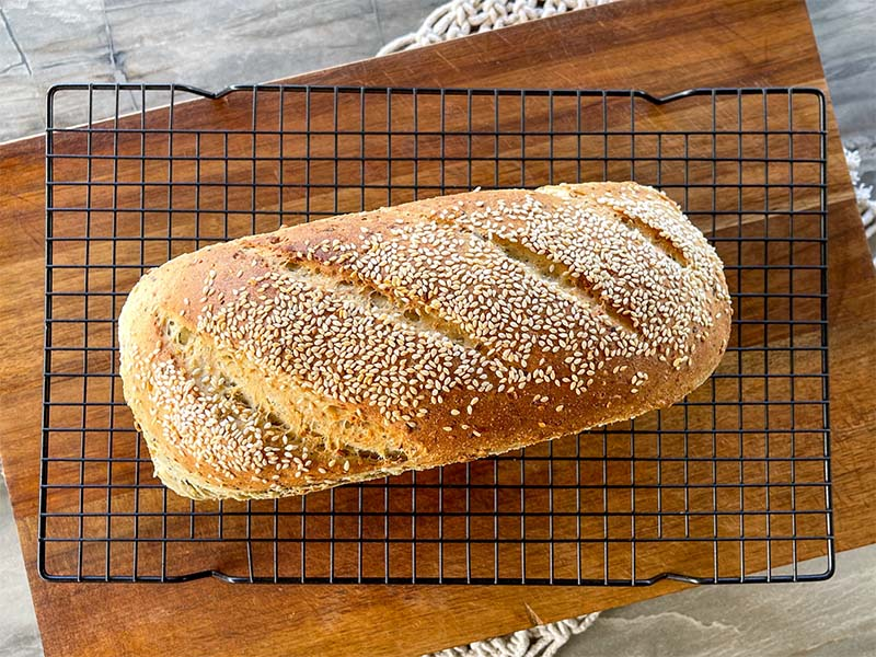 super seeded wholemeal multigrain thermomix bread Birdseye view of whole loaf, sesame seeds on top. Sitting on black mesh cooling rack on top of brown cutting board on top of grey bench top