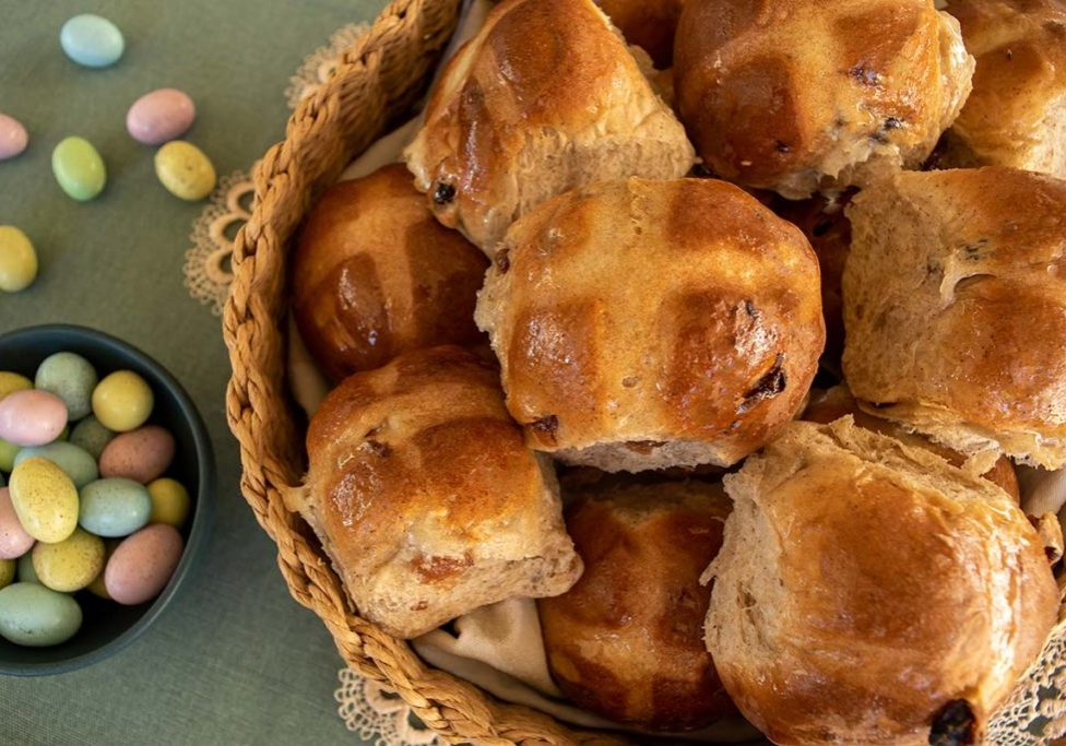 Basket packed full of hot cross buns that have been whipped up in thermomix, small bowl full of candied Easter eggs to the left with some on the tabletop also. Background is a green placemat and cream doily.